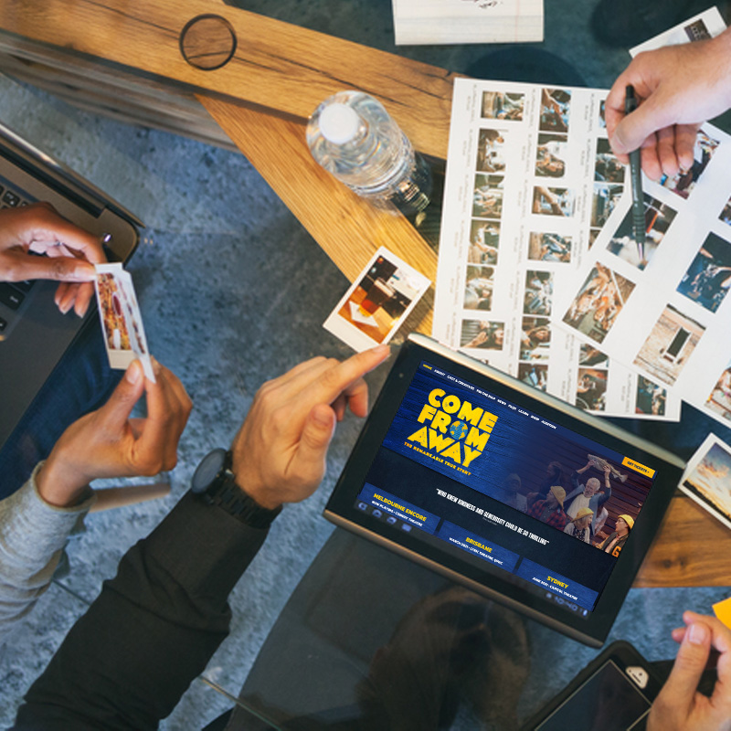 Group of designers brainstorming with Come From Away website on tablet